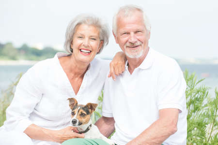 Smiling and actice senior couple with dog photo