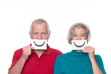 Senior couple with smiley and unhappy sign in front of white background photo