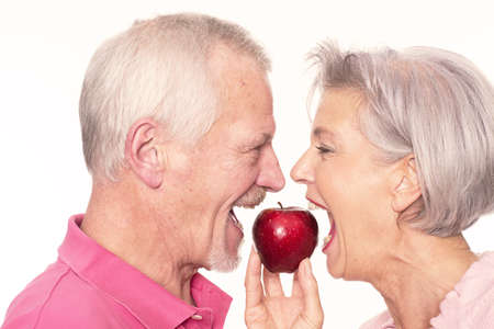 woman apple: Senior couple with apple in front of white background