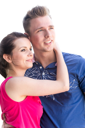 young couple smiling: Young couple in front of white sky