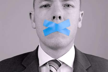 mouth closed: Joven hombre de negocios con cinta adhesiva. Foto se hizo en un estudio