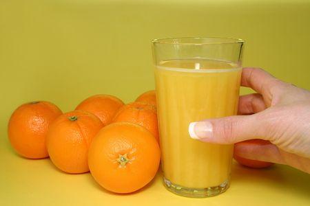 tomando refresco: vaso de jugo de naranja con toda la orage sobre fondo amarillo  Foto de archivo