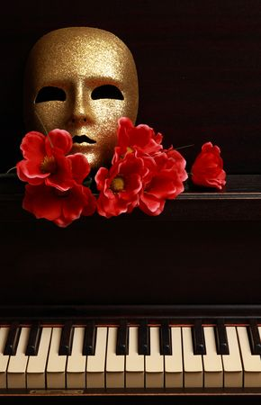 gold mask and red flower on a piano LANG_EVOIMAGES