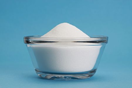 bowl filled with white sugard, blue background Stock Photo - 4006866
