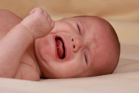 caucasian baby girl crying, beige background