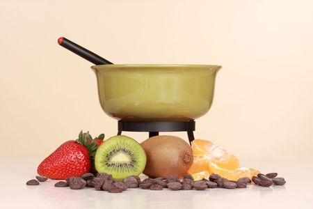 chocolate fondue kit and fresh fruit, beige background Stock Photo - 4900584
