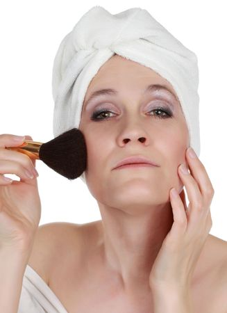 fourties: early fourties woman with white towel on head applying blush