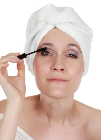 fourties: early fourties woman with white towel on head applying mascara LANG_EVOIMAGES