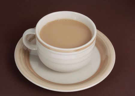 beige: beige cup filled with milk coffee, brown background