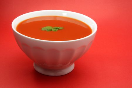 tomato soup in a white bowl, red background photo
