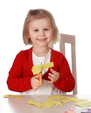 Cute little girl, coupant la feuille de papier jaune Banque d'images - 7185513