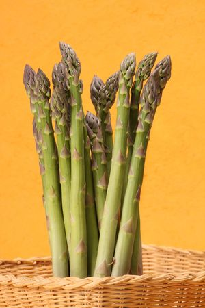 closeup on uncooked asparagus in wicker basket photo
