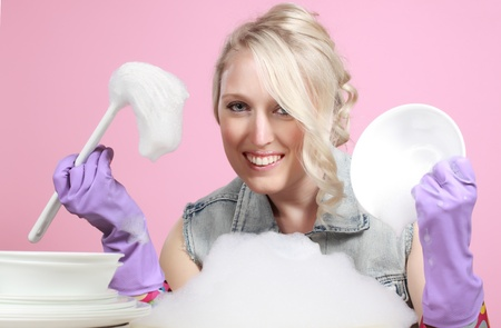 rubber: cute young blond woman washing dishes, pink background