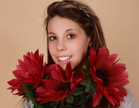 fake smile: portrait of a beautiful young caucasian woman with fake flowers Stock Photo