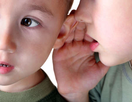 listening ear: The boy whispering in an ear to the younger brother.