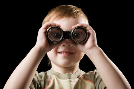 The child watching with binoculars. Isolated on a black background.