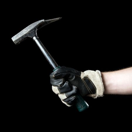 Hammer in hand. Isolated on a black background. photo