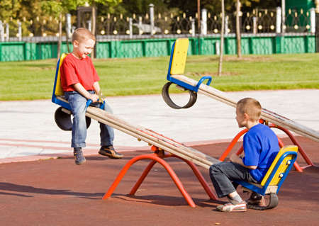 Boys playing on a seesaw on a playground in a sunny day photo