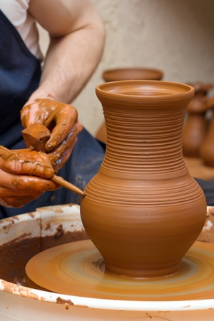 Close-up of hands making pottery on a wheel photo