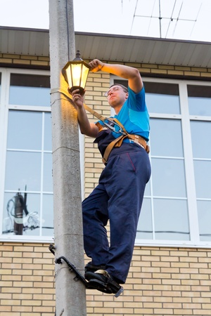 lamp on the pole: electrician replace the lamp on a pole Stock Photo