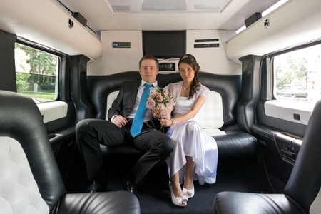 Portrait young happy bride and groom in car photo