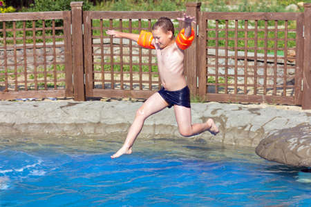 child jumps into the pool with water photo