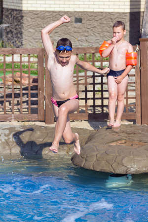 Boy jumps into the pool with water Stock Photo