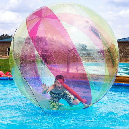 ball on water: Boy in a ball on the water. Water Zorbing