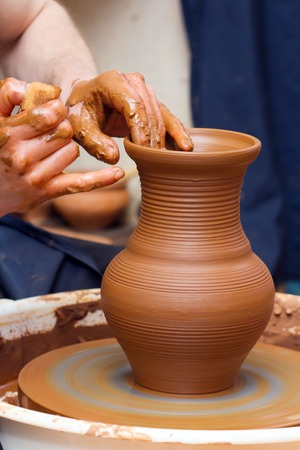 clay craft: Close-up of hands making pottery on a wheel Stock Photo