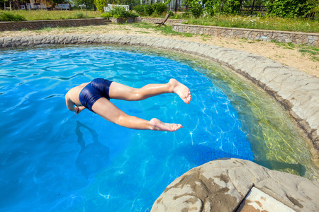 plunge: Teen dives into a swimming pool with springboard