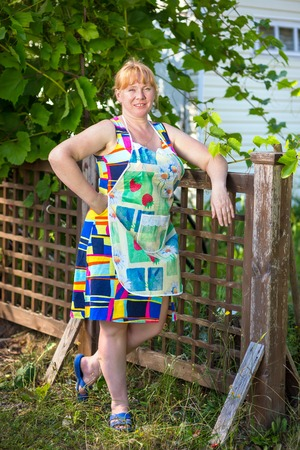 40 45: Rural women in an apron standing at fence