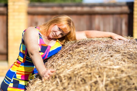 red haired: Portrait of a woman near a haystack Stock Photo