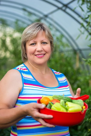 Portrait of a woman with vegetables in a bowl near greenhouses photo