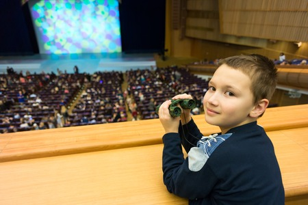 amphitheater: 9-year boy with binoculars in a theater amphitheatre Editorial