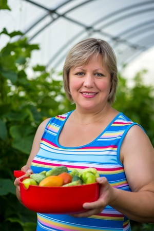 Portrait of a middle-aged woman with vegetables in a bowl near greenhouses photo