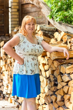 40 45: Portrait of a rural middle-aged red-haired women near woodpile