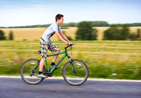 country boy: Teen riding a bike on country road