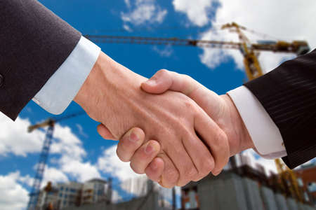 Two business men shaking hands on a background of construction