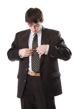 corrects: Young man in dark suit corrects tie
