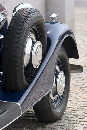 hubcaps: Front side of dark blue retro Cadillac  Ïåðåäíåå è çàïàñíîå êîëåñà ðåòðî àâòîáîìèëÿ Êàäèëëàê