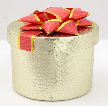 Little golden present box with big red bow on top. photo
