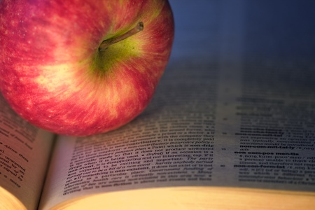 Delicious red apple on a book photo