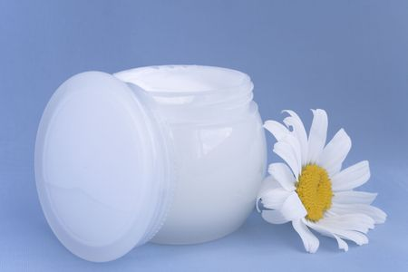 moisten: Cream for a body and face decorated camomile flower isolated on blue Stock Photo