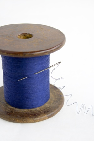 needlecraft product: Spool of blue thread with a needle on a white background