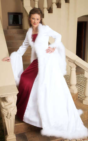 Beautiful smiling bride in red and white satin dress with feather coat, on the stairs Stock Photo - 885882