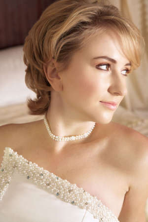 Beautiful bride with short blond hair in pearl beaded dress and soft make-up