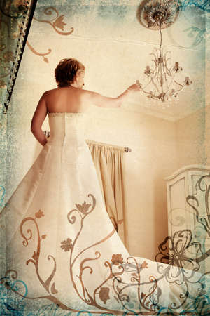 Beautiful bride in white dress on grunge romantic floral background touching antique chandelier photo