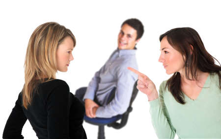 accusing: Neatly dressed brunette pointing accusing finger at a blond woman with a smiling man on a chair in the background