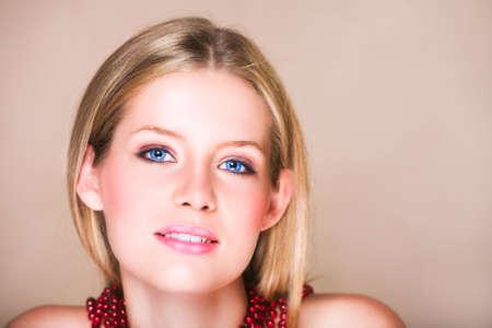 loose hair: Adolescenti ragazza bionda con i capelli sciolti direttamente sul beige con sfondo rosso brillante collana e morbido sorriso. Naturale make-up, ha pelle.