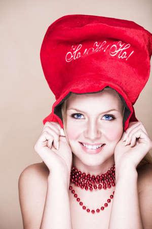 cappello natale: Biondo ragazza adolescente a sfondo beige con il rosso brillante collana e il Natale con cappello Ho! Ho! Ho! Ridendo.